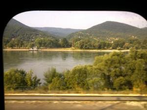 Pohľad cez nástupné dvere vozňa z vlaku 477 na Dunaj a okolité kopce.